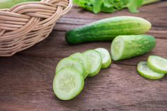 Fresh cucumber and slices on wooden table Stock Image