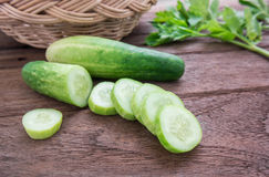 Fresh cucumber and slices on wooden table. Fresh cucumber and slices on a wooden table Royalty Free Stock Photo