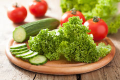 Fresh cucumber tomatoes and salad leaves on chopping board Royalty Free Stock Photography