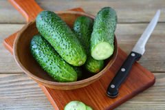Fresh cucumbers in a clay bowl on cutting board Stock Photos
