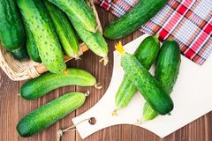 Fresh cucumbers on the cutting board and in a basket. On a wooden table Royalty Free Stock Photography
