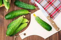 Fresh cucumbers on the cutting board and knife. On a wooden table. Top view Royalty Free Stock Image