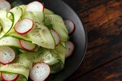 Fresh cucumbers, radish salad with salt, pepper and lemon stock photos