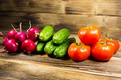 Fresh cucumbers, radishes and tomatoes on wooden table Royalty Free Stock Photos