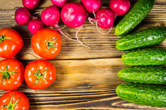 Fresh cucumbers, radishes and tomatoes on wooden table Stock Photography