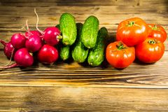 Fresh cucumbers, radishes and tomatoes on wooden table Stock Images