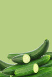 Fresh cucumbers and some cut pieces. On a green background Royalty Free Stock Photography
