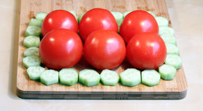 Fresh cucumbers and tomatoes. On a wood chopping board Stock Image