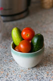 Fresh cucumbers and tomatoes in a glass on the table. Fresh cucumbers and tomatoes in a bowl Stock Photo