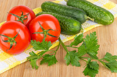 Fresh cucumbers and tomatoes with parsley on napkin Stock Photography
