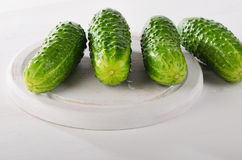 Fresh cucumbers on white cutting board. Royalty Free Stock Photos