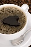 A fresh cup of black coffee. A cup of black coffee on a background of beans Stock Photos