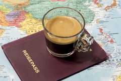 Fresh cup of coffee, passport and map. Fresh cup of coffee, passport and world map in a conceptual image of travel and tourism Royalty Free Stock Photo