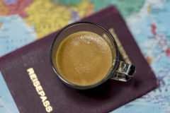 Fresh cup of coffee and passport on a map. Fresh cup of coffee and passport on a world map viewed from above in a concept of travel, tourism and vacations Stock Images