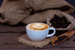 Fresh cup of coffee and beans. Fresh cup of coffee with roasted beans and hessian sack in background Royalty Free Stock Photos