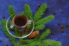 A fresh Cup of coffee on a saucer and fir tree branches on blue Stock Image