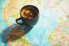 Fresh cup of coffee with world map in the background. Conceptual image of travel trip planing with world map; travel related background stock image