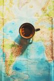 Fresh cup of coffee with world map in the background. Conceptual image of travel trip planing with world map; travel related background royalty free stock photo