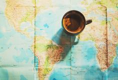 Fresh cup of coffee with world map in the background. Conceptual image of travel trip planing with world map; travel related background stock photos