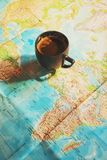 Fresh cup of coffee with world map in the background. Conceptual image of travel trip planing with world map; travel related background royalty free stock images