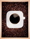 Fresh cup of dark coffee in box with roasted beans Stock Images