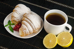 Fresh cup of hot black coffee with croissants and lemon Stock Photos