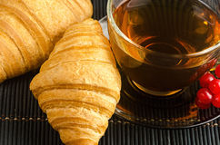 Fresh cup of hot black tea with croissants Royalty Free Stock Image
