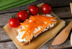 Fresh curd cheese on bread with carrot Royalty Free Stock Images