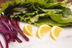 Fresh cut beet stems, leaves and lemon wedges Stock Photos