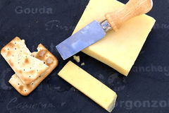 Fresh cut cheddar cheese with crackers on a slate board Royalty Free Stock Images