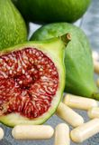 Fresh cut figs. Healthy fresh cut green figs on table with vitamin supplements Stock Image