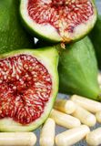 Fresh cut figs. Healthy fresh cut green figs on table with vitamin supplements Stock Photo
