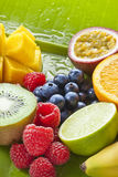 Fresh Cut Fruit. Fresh fruit including blueberries raspberries, orange, lime, banana, mango, passion fruit and kiwi fruit on a green banana leaf sprayed with Royalty Free Stock Image