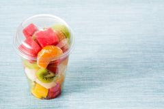 Fresh cut fruit in a plastic cup. On blue background. Copyspace royalty free stock photos