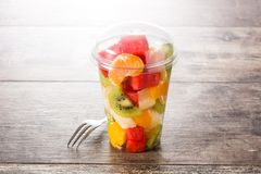Fresh cut fruit in a plastic cup on wood. En table royalty free stock photography