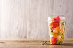 Fresh cut fruit in a plastic cup on wood. En table. Copyspace royalty free stock photography