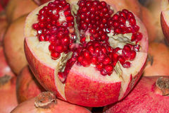 Fresh cut fruit pomegranate on the background of other garnets. Closeup Royalty Free Stock Images