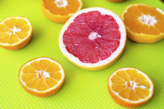Fresh cut fruits citruses on a green  background. Royalty Free Stock Photos