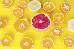 Fresh cut fruits citruses on a yellow  background. Stock Image