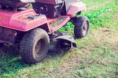 Fresh cut grass flying from riding lawnmower person cutting long. Green grass with a riding lawn Royalty Free Stock Photo