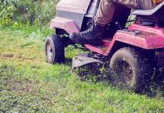 Fresh cut grass flying from riding lawnmower person cutting long. Green grass with a riding lawn Royalty Free Stock Image