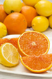 Fresh cut lemon and orange. Fresh cut orange and lemon on a plate with whole oranges and lemons in background on a white tablecloth stock images