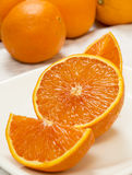 Fresh cut orange. On a plate with whole oranges in background on a white tablecloth stock photo