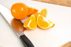 Fresh cut oranges on cutting board with knife Stock Images