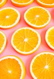 Fresh cut oranges on pink background. Selective focus Royalty Free Stock Photography