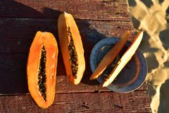 Fresh cut papaya slices rustic wood table beach, Baja, mexico. Fresh cut slices of ripe papaya served on a rustic wood table on the sand beach shore of the Sea Royalty Free Stock Photos