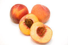 Fresh Cut Peaches. Fresh peaches with one cut open on a white background Stock Photography