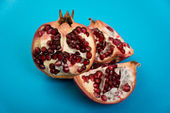 Fresh cut pomegranate. Red fresh cut pomegranate on blue background Stock Photography