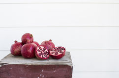 Fresh Cut Pomegranates on weathered wooden table, isolated Royalty Free Stock Photography