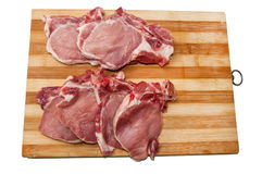 Fresh cut pork chops on wooden board Stock Images